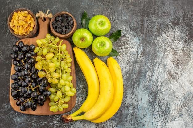 Фрукты виноград на доске сухофрукты бананы три яблока с листьями