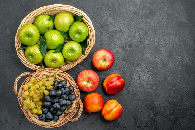 Frutta mele verdi nel cesto nettarine e grappoli d'uva