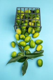 파란색 테이블에 회색 바구니에 잎이 있는 과일 녹색 과일