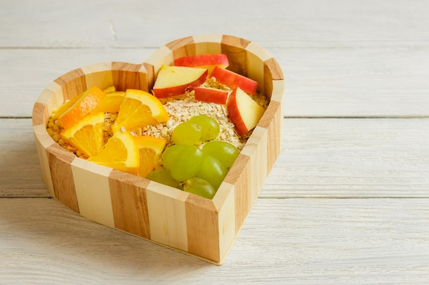 木製の背景にフルーツの心。健康食品のコンセプトです。