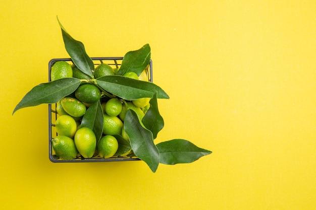 식탁에 잎이 달린 녹색 감귤 바구니에 담긴 과일