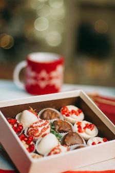 Фрукты в шоколаде в коробке на столе