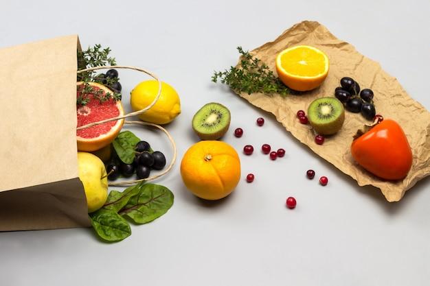 紙袋に入った果物。紙に柿、キウイ、ブドウ、レモン。灰色の背景。フラットレイ。コピースペース