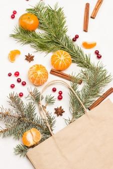 紙袋に入った果物。みかん全体、皮をむいたみかんのくさび。クランベリーとスパイス、テーブルの上のモミの小枝。フラットレイ