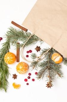 紙袋に入った果物。みかん全体、皮をむいたみかんのくさび。クランベリーとスパイス、テーブルの上のモミの小枝。白色の背景。フラットレイ