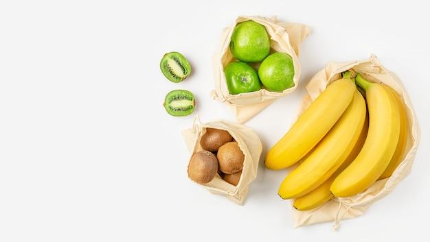 흰색 표면에 플라스틱 무료 에코 가방에 과일. 바로 위에 복사 공간