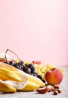 Фрукты в многоразовой хлопчатобумажной текстильной белой сумке на сером и розовом фоне. концепция хранения и переработки отходов.
