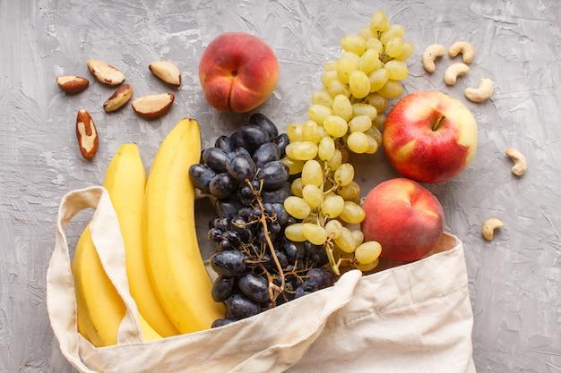 Плоды в хлопчатобумажной текстильной белой сумке на сером бетонном фоне.