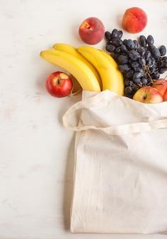 白い木製の背景に再利用可能な綿繊維白いバッグの果物。廃棄物ゼロのショッピング、保管、リサイクルのコンセプト。トップビュー、フラットレイアウト、