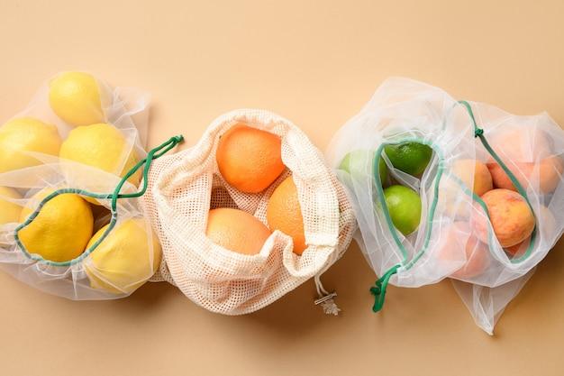 Плоды в многоразовых экологически чистых мешочках на жёлтом. ноль отходов. экологическая концепция. стоп загрязнения.