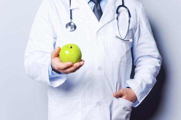과일은 당신을 건강하게 만듭니다. 회색 배경에 서 있는 동안 녹색 사과를 들고 있는 의사의 클로즈업