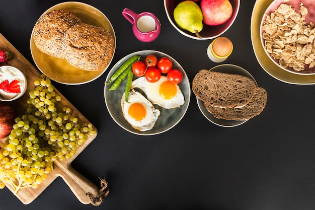 Fruits, muesli, fruits and fried omelette with tomatoes and peas on black background