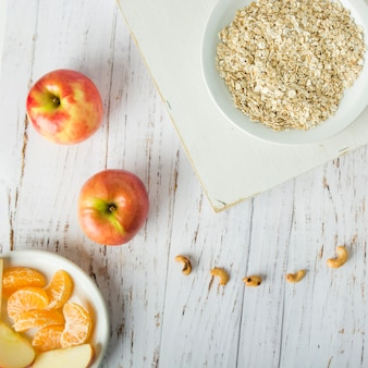 Fruits near bowl with oatmeal