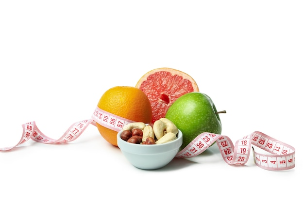 Fruits, nuts and measuring tape isolated on white