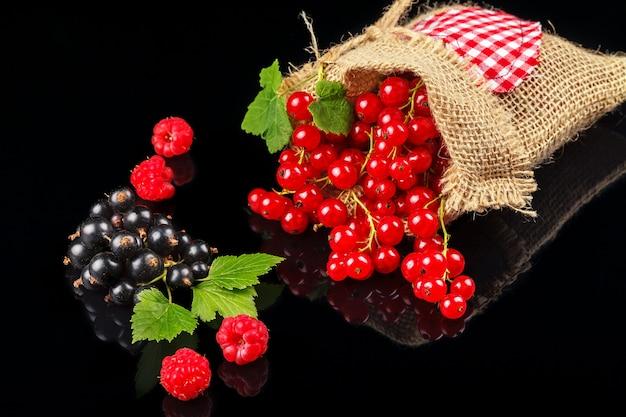 Плоды малины, черной смородины и красной смородины на темном фоне.