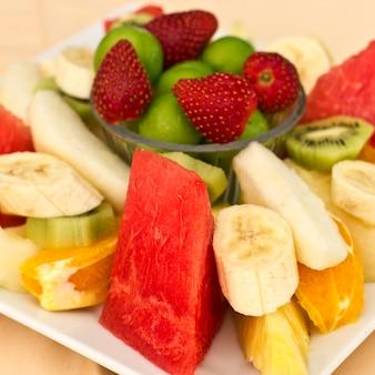 皿の上の果物。グリーンプラム、イチゴ、バナナ、キウイ、スイカ、オレンジ、アップル。