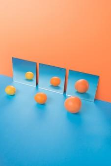 ミラーの近くのオレンジに分離された青いテーブルの上の果物
