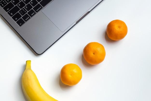 職場での果物ノートパソコン、バナナ、みかん、白い机の上のオレンジジュース。