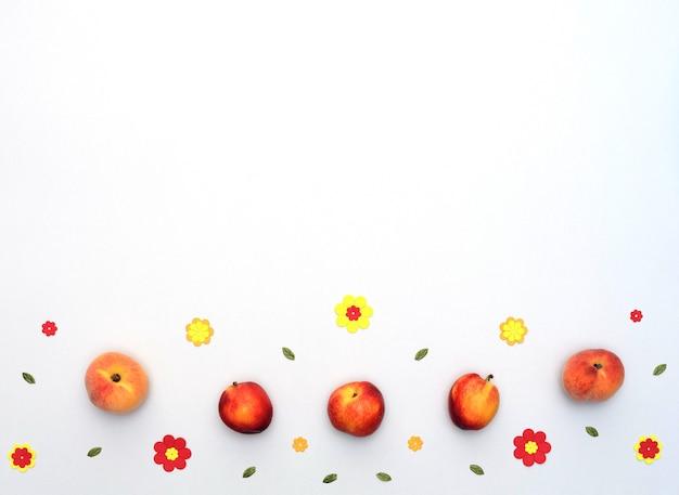 Фрукты персики и нектарины с яркими бумажными цветами на белом фоне в плоском стиле