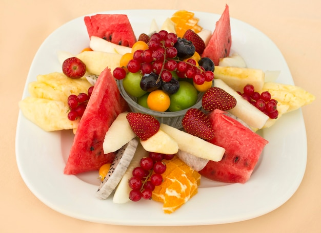 Fruits on a plate. green plum, red currant, blueberry, strawberry, physalis, pitahaya