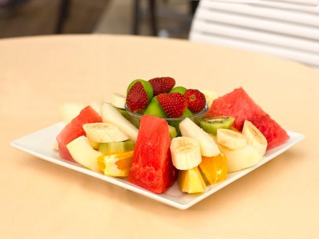 Fruits on a plate. green plum, strawberry, banana, kiwi, watermelon, orange and apple.