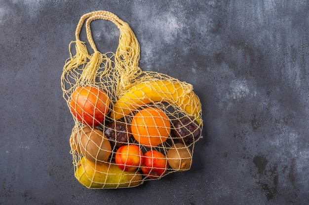 Fruits in the range in yellow eco string bag on a dark wooden surface
