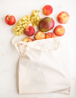 Fruits in reusable cotton textile white bag on white wooden background zero waste shopping storage and recycling concept flat lay