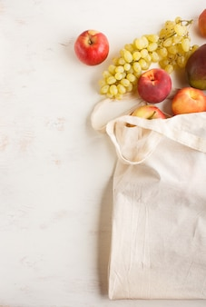 Fruits in reusable cotton textile white bag on white wooden background. zero waste shopping, storage and recycling concept. top view, flat lay, copy space.