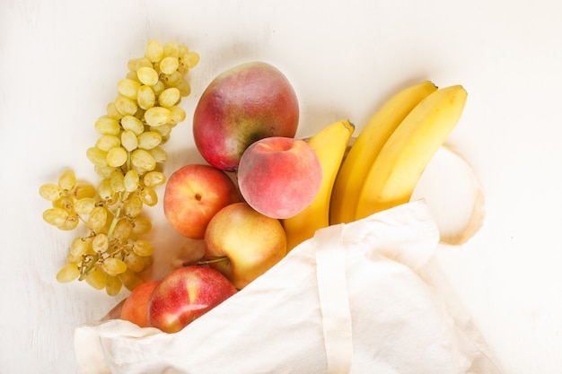 Fruits in reusable cotton textile white bag on white wooden background zero waste shopping storage and recycling concept