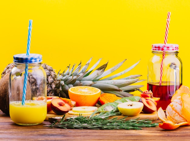 Fruits; rosemary and juice mason jar on chopping board against yellow backdrop
