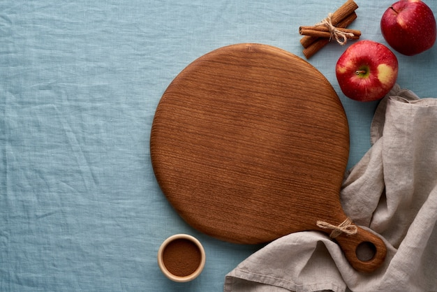 Fruits and round wooden cutting board on blue linen tablecloth