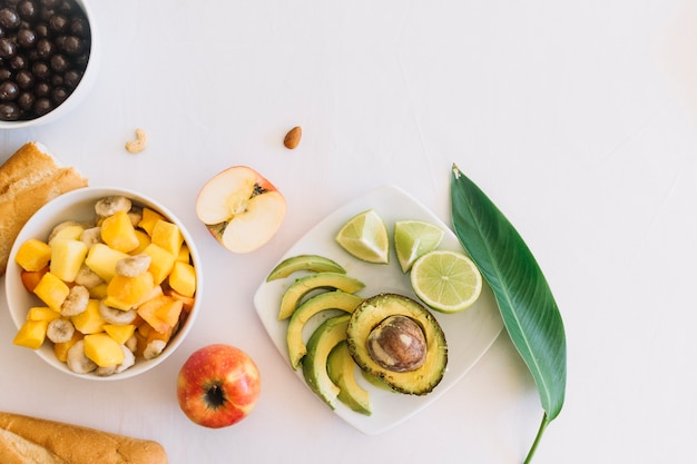 Fruits salad and bread on white backdrop