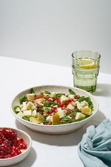 Фруктовый салат с орехами, сбалансированное питание. жесткий свет, тени. шпинат с яблоками, орехами пекан, вертикальный