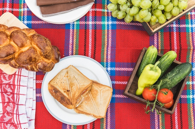 Fruits; sandwiches and baked braided bread loaf on checkered tablecloth