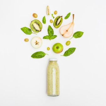 Fruits smoothie in closed bottle against white background