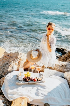 Fruits, snacks, and drinks during sea picnic. girl doing cheatmeal on sea side with rocks, dressed in white elegant dress, straw hat. tourism agriculture trip concept. travel to south countries