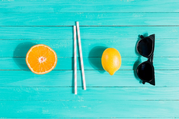 Fruits, straws and sun glasses in order
