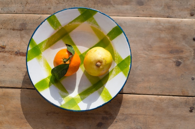 Fruits tangerine and pear in vintage porcelain dish plate