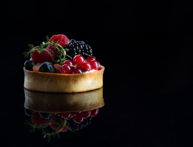 Fruits tartlet with fresh raspberries, blueberries and ment on black wall