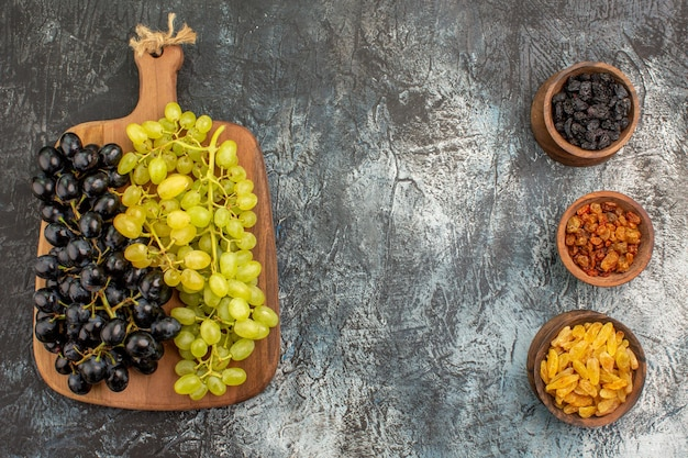 Fruits three bowls of dried fruits green and black grapes on the cutting board