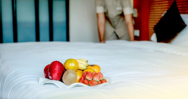 Fruits in tray in front of hotel maid making the bed in the luxury hotel room ready for tourist travel.