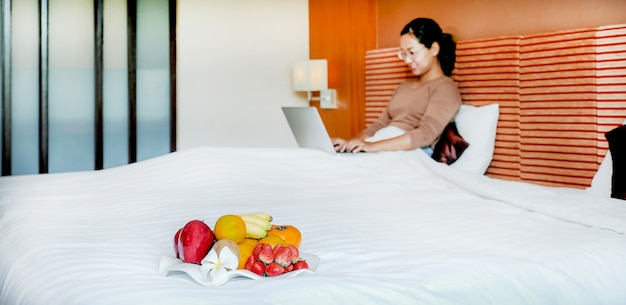 Fruits in tray in front of tourists used laptop on the bed in the luxury hotel room.