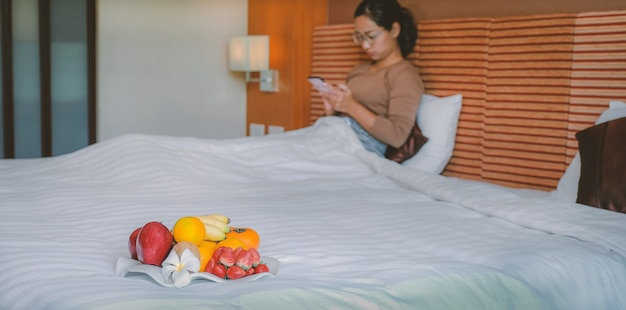 Fruits in tray in front of tourists used smartphone on the bed in the luxury hotel room.