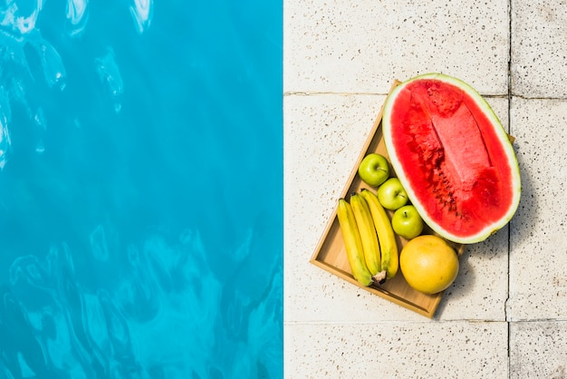 Fruits on tray placed on border of pool
