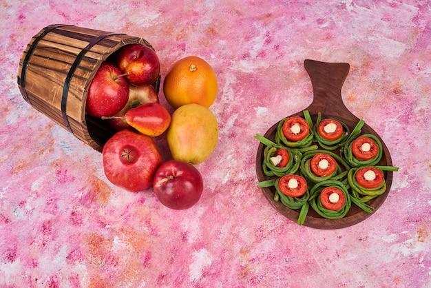 Spuntino di frutta e verdura su un piatto di legno.