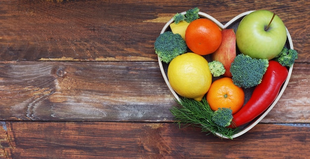 Fruits and vegetables in heart shaped wooden box. broccoli, apples, pepper, tangerine over wooden table. health food concept with copyspace.