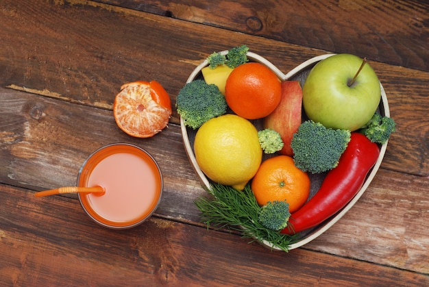 Fruits and vegetables in heart shaped wooden box. broccoli, apples, pepper, tangeriners.
