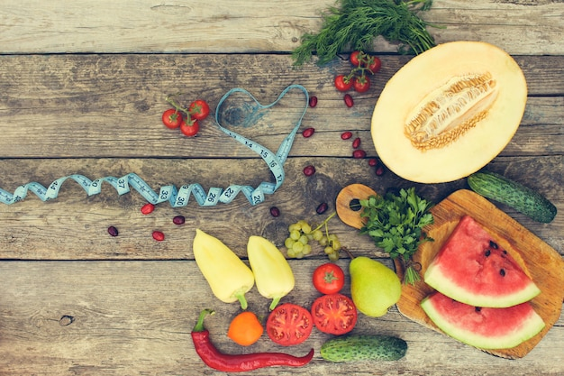 Fruits, vegetables and in measure tape in diet on wooden background. toned image.