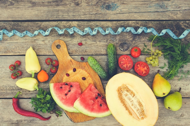 Fruits, vegetables and in measure tape in diet on wooden background.