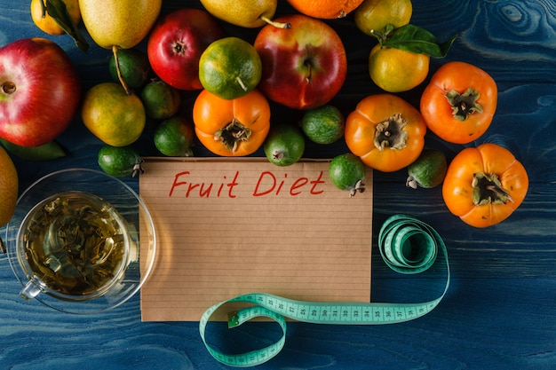 Fruits, vegetables and in measure tape in diet on wooden background